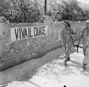 British soldiers smile at a 'Viva Il Duce' slogan on a wall in Reggio, Italy, September 1943
